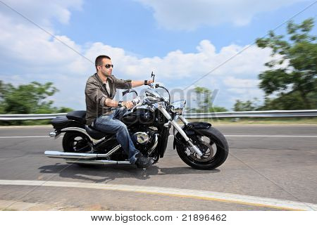 A young man riding a motorcycle on an open road