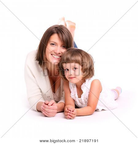 A portrait of a mother and her baby girl lying on the floor and smiling over white background