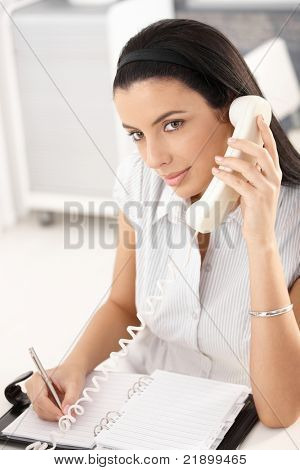 Pretty office girl working at desk, taking notes into personal organizer, concentrating on landline phone call.?