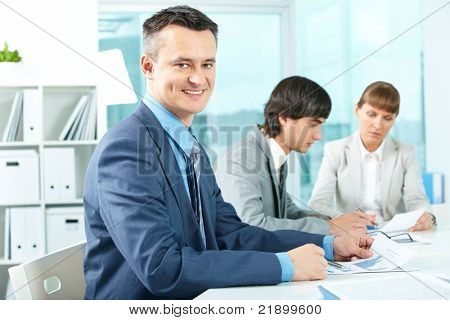 Successful businessman looking at camera in working environment