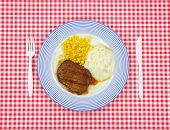 foto of frozen tv dinner  - Salisbury steak dinner with corn and potato on a blue striped plate with plastic silverware on a red checkerboard cloth - JPG
