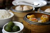 stock photo of siomai  - chinese style cuisine pork sioami and prawn dumplings in bamboo steamers served filipino style with calamansi in a restaurant in manila - JPG