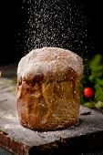 closeup of a panettone, a typical Italian sweet for Christmas time, sprinkled with icing sugar, on a rustic wooden table