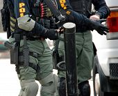 stock photo of raid  - two SWAT team members putting on raid gear before an operation - JPG