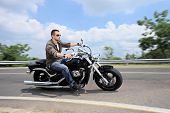 foto of rebel  - A young man riding a motorcycle on an open road - JPG