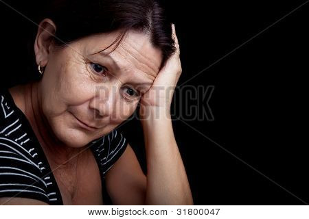 Portrait of a very sad and depressed older woman suffering from stress or a strong headache isolated on black