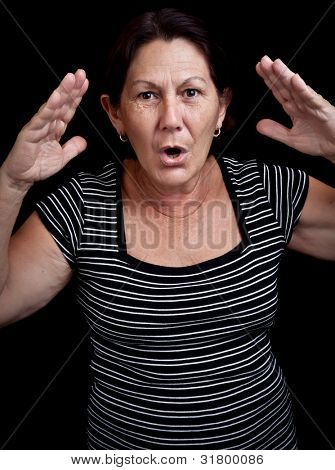 Portrait of an old woman screaming and gesturing with her hands isolated on a black background