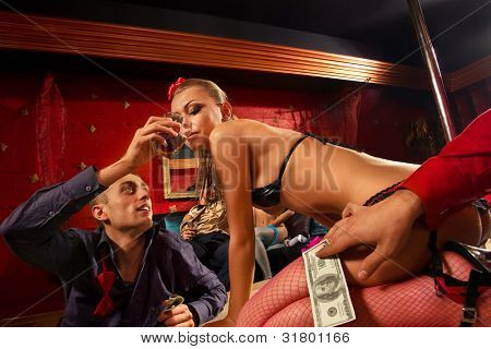 Man giving glass of whiskey to stripteaser woman on stage