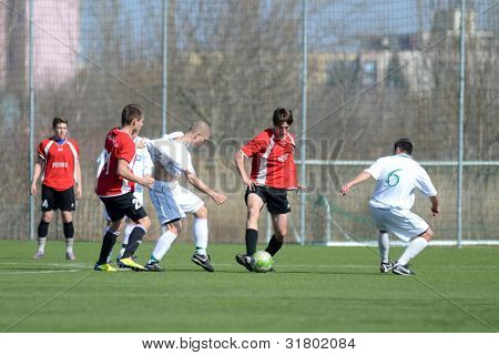 KAPOSVAR, HUNGARY - MARCH 16: Attila Kiss (white 5) in action at the Hungarian National Championship under 19 game between Kaposvar (white) and Szentlorinc (red) on March 16, 2012 in Kaposvar, Hungary.