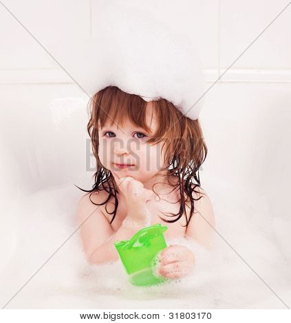 thoughtufl one year old girl taking a bath with foam and holding shampoo in her hands