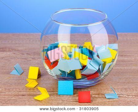 Pedazos de papel para la lotería en florero en la mesa de madera sobre fondo azul