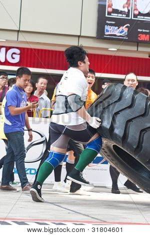 TOA PAYOH, SINGAPORE - MARCH 24 : Contender for Strongman Samuel Lim attempting the six times 350kg tyre flip category in the Strongman Challenge 2012 on March 24, in Toa Payoh Hub, Singapore.