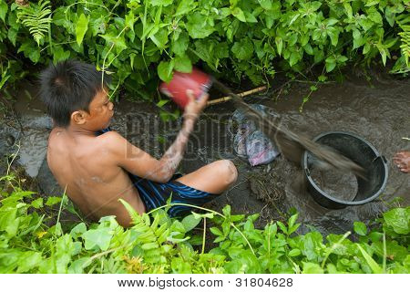 BALI, INDONESIA - MARCH 31: Unidentified poor kid catches small fish in a ditch near a rice field on March 31, 2012 on Bali. Daily caloric intake per capita in Indonesia is 2891 kcal per person.