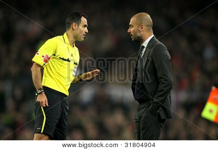 BARCELONA - MARCH 3: Referee Velasco Carballo talks with Pep Guardiola of Barcelona during the Spanish league match against Sporting Gijon at the Camp Nou stadium on March 3, 2012 in Barcelona, Spain
