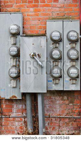 Ocho antiguo resistido medidores de potencia oxidado en una pared de ladrillo rojo y naranja