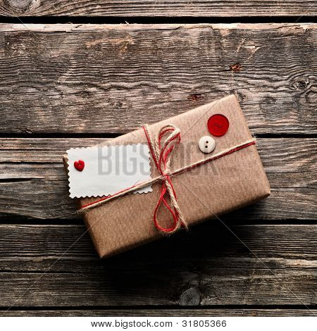 Vintage gift box (package) with blank gift tag on old wooden background.