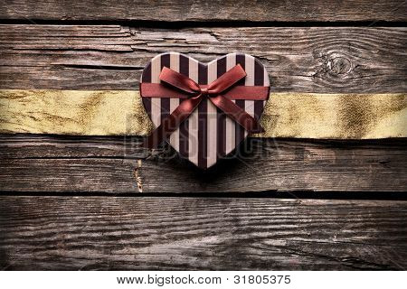 Heart shaped gift box with golden ribbon on old wood. Vintage holiday background.