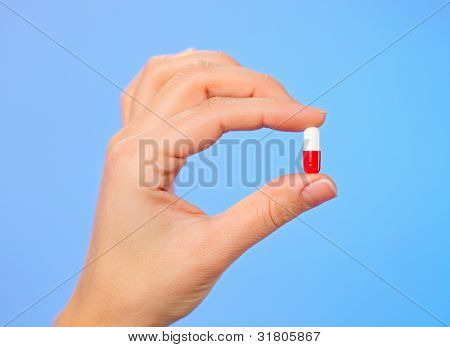 Red and white bolus (capsule) in doctor hand, macro view