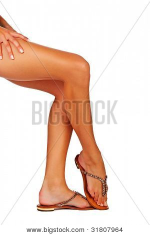 Closeup of a young woman tanned legs in summer fashion sandals on white studio background