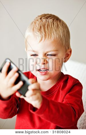 upset little 3 year old boy is frustrated with the media player or electronic toy he is holding