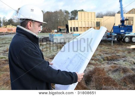 Construction worker examining a blueprint