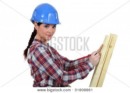 female carpenter taking measurements of a board
