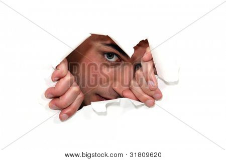 Man looking through a ripped paper wall.
