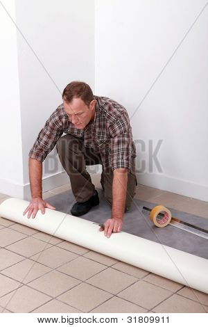 Man unrolling carpet roll