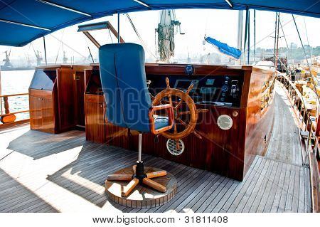 Cockpit inside a boat with a wood wheel and leather chair.