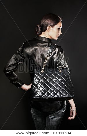 Beautiful woman with black bag on black