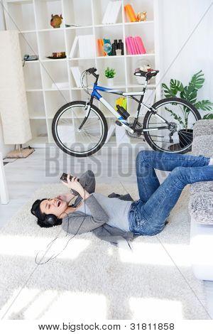 girl lying on floor in living room and listening music through smart phone