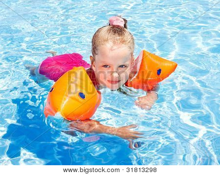 Child with armbands in swimming pool. Summer outdoor.