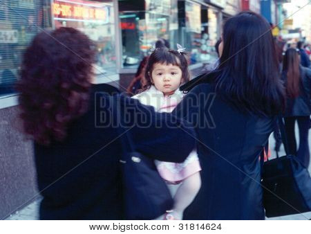 NEW YORK - CIRCA AUGUST 1997: Two women pass a young unidentified child to the other as they walk on a street in Chinatown circa August 1997 in New York City.