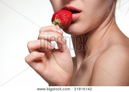 Young woman biting strawberry isolated on white
