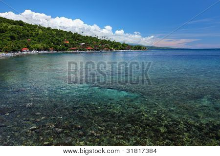 Tropical lagoon with clear water and buildings in forest on a hillside. Amed village, Indonesia