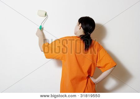 The young woman painting a wall