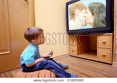 Rear view of little boy sitting on the floor and watching cinema  on TV at home
