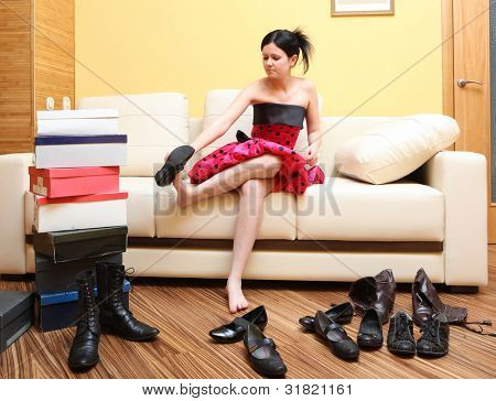 Young attractive model sitting on the sofa also chooses shoes