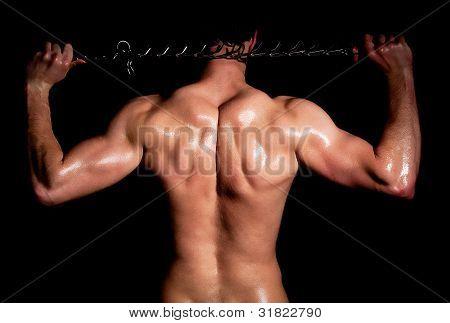 Moda homem musculoso em uma pose de moda com cadeia