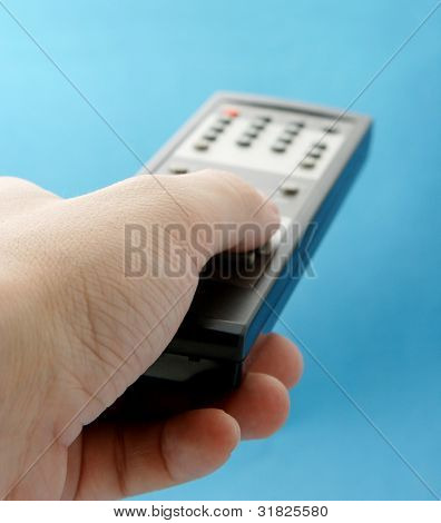Hand pointing a TV remote control towards the television