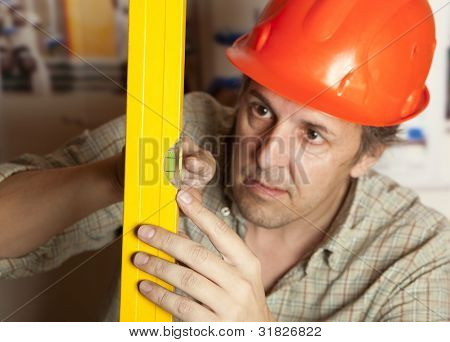 Worker checking vertical level with bubble level tool