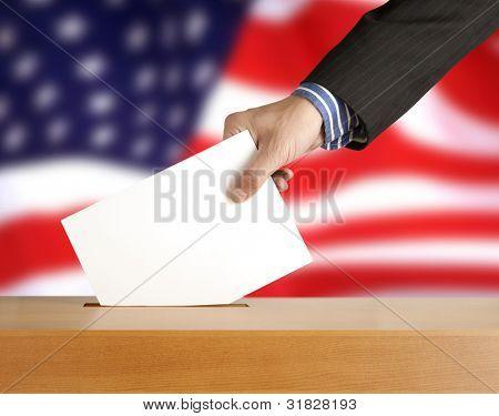 Mano con boleta y la caja en la bandera de Estados Unidos