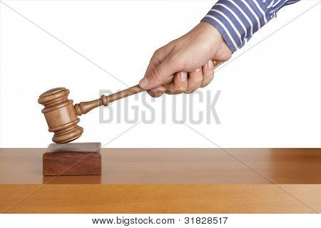 Human hand holding a wooden gavel