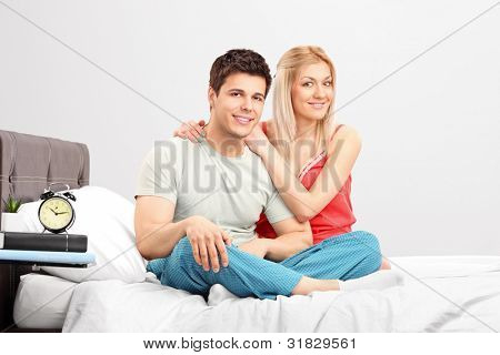 A lovely couple in pijamas sitting on a bed