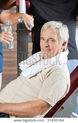 Elderly man with towel relaxing on bench in fitness center