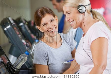 Happy fitness trainer coaching senior woman in gym