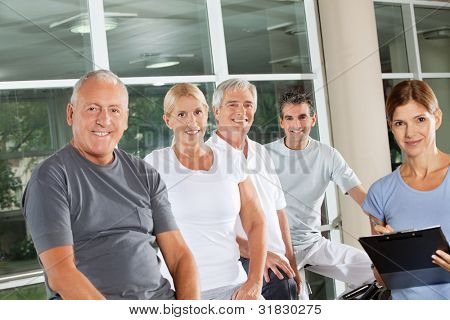 Group of happy senior people with fitness trainer in gym