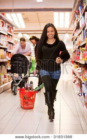 An asian woman in a grocery store with an ipad and basket