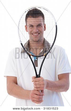 Young tennis player smiling happily holding tennis racket front of his face.