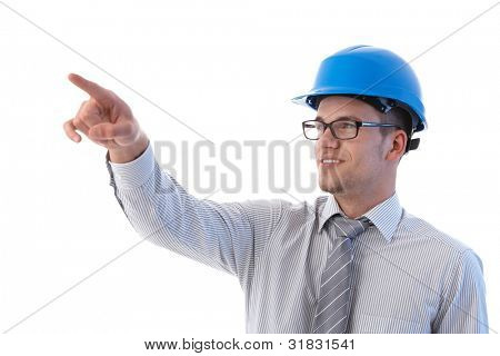 Young architect at construction site pointing to distance, smiling.